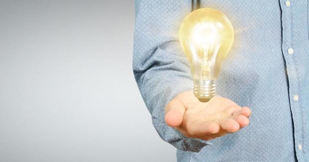 照らされた電球、技術革新のインスピレーションコンセプトを持っている手
