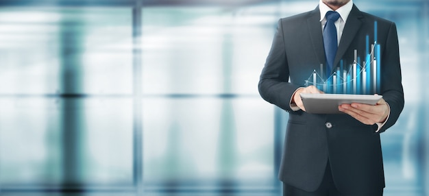 Бизнесмен с графом в его бизнес-планшет в руке