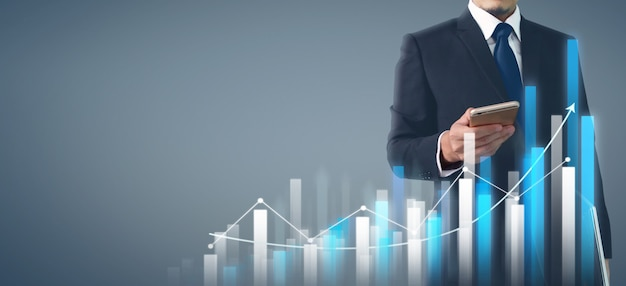Бизнесмен план график роста и увеличения диаграммы бизнес-телефон в руке