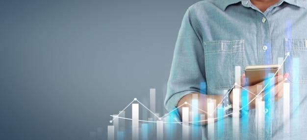 スマートフォンデバイスを押しながら画面に触れる手。証券取引所市場のコンセプト