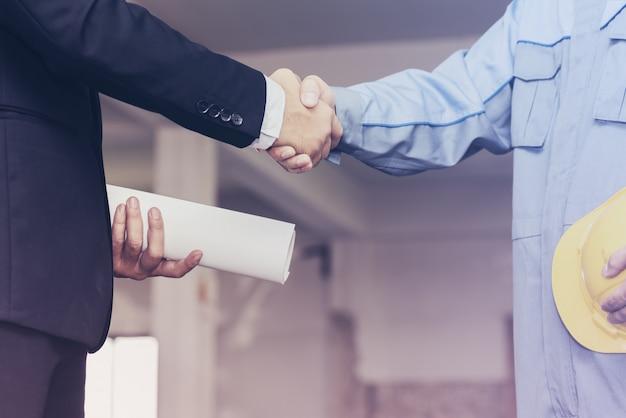 サイト上でビジネスマンと握手をする建築家エンジニア