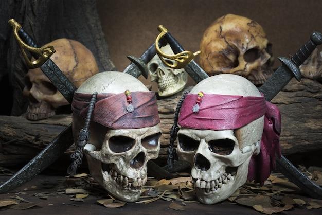 Два пиратских черепа над тремя человеческими черепами в лесу