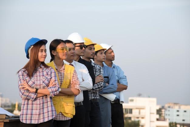 立っている現場を見ているエンジニアと建築家のグループ