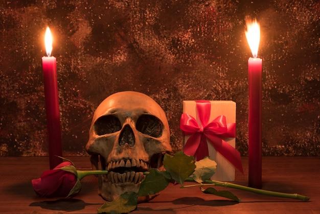 人間の頭蓋骨、プレゼント、ローズ、キャンドル、木製テーブルでの静物画写真撮影