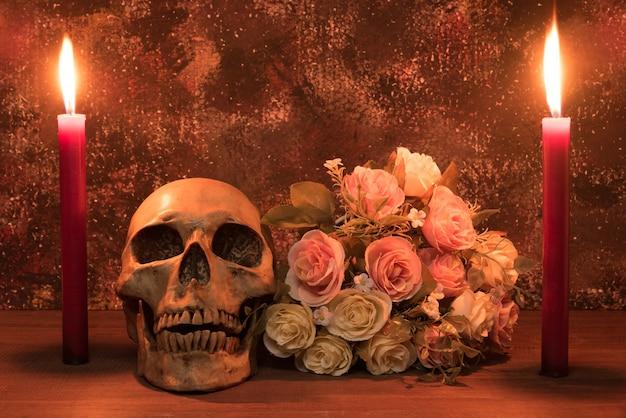 人間の頭蓋骨、ローズ、キャンドル、木製のテーブルでの静物画撮影
