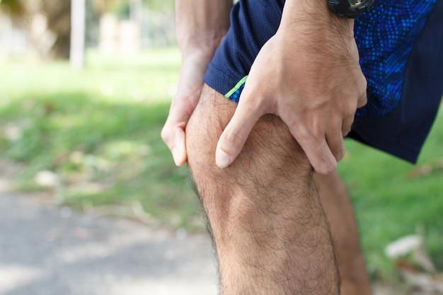Закройте вверх человека спорта страдая с болью на ушибе колена спорт идущем после бежать. ушиб от концепции разминки.