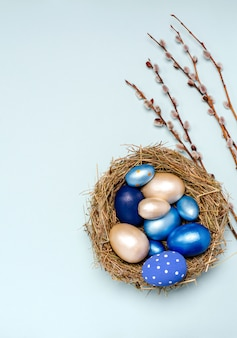 ヤナギの枝が付いているわらの巣の青いトーンのイースターエッグ。
