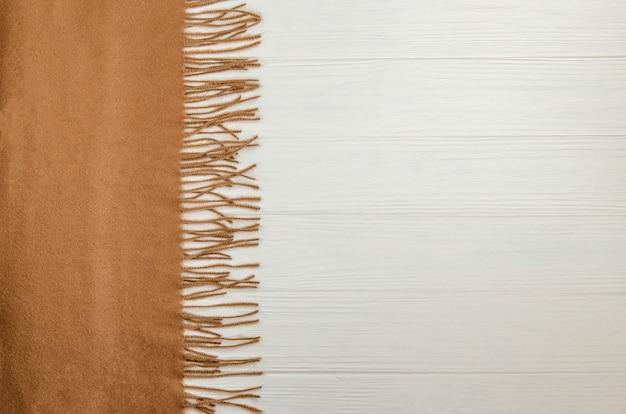 Осенний фон с шерстяным теплым шарфом бежевого цвета.