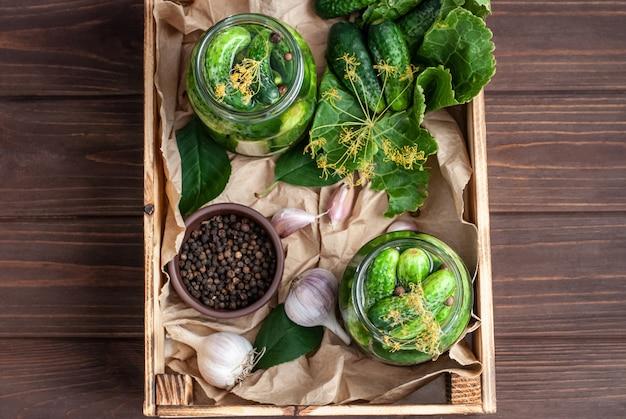 Ферментация огурцов в стеклянных банках. сырые огурцы, цветы укропа, вишневый лист, лист хрена, специи и травы на подносе