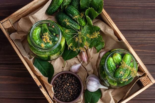 Ферментация огурцов в стеклянных банках. сырые огурцы, цветы укропа, лист вишни, лист хрена, специи и травы на подносе в стеклянных банках