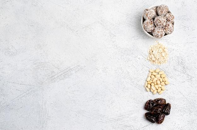Энергетические шарики в белой тарелке и ингредиенты финики, овес, арахис для их приготовления, плоская планировка, копия пространства