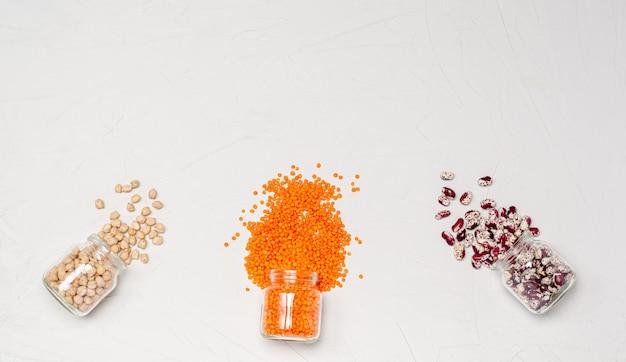 ガラス瓶入りのベジタリアン向けのさまざまな乾燥シリアル:ひよこ豆、オレンジ色のレンズ豆、白い表面に紫の豆。