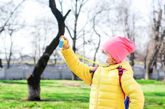 検疫中に防護マスクを着た小さな女の子が春に屋外で散歩し、子供用カメラでセルフィーを撮ります。