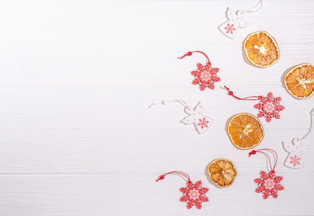 Елочные деревянные игрушки в виде белого ангела, красной снежинки, сушеные апельсиновые дольки для украшения с местом для копирования пространство с плоской лежал на белом фоне.