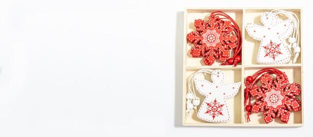 白い天使とフラットでコピースペースのための場所で装飾のための木箱に赤い雪の結晶の形でクリスマス木製おもちゃは、白い背景に横たわっていた。
