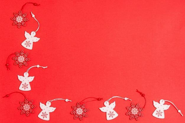 白い天使と赤の背景に赤の雪片の形でクリスマスの木製おもちゃ。