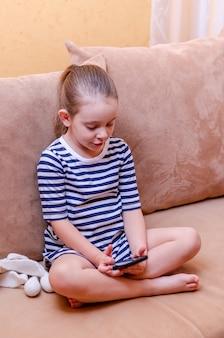 Маленькая милая девушка делает селфи на смартфоне дома