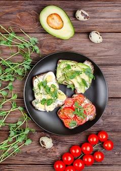 Разнообразие мини-бутербродов со сливочным сыром и овощами в черной терке на деревянной поверхности