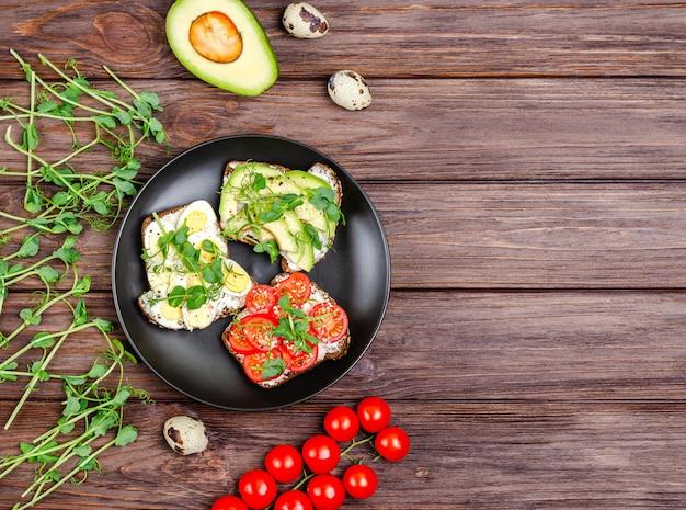 Разнообразие мини-бутербродов со сливочным сыром и овощами в черной тарелке