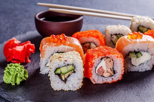 Сет суши ролл с лососем, угрем, тунцом, авокадо, огурцом, сливочным сыром филадельфия, икрой тобик, на черной грифельной доске