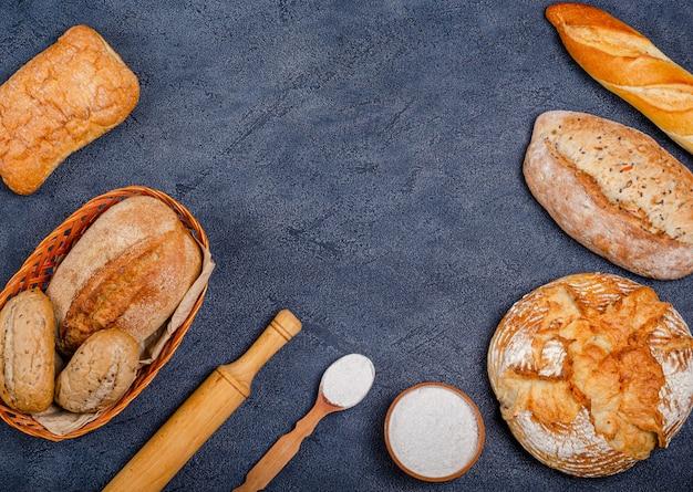 Пекарня - различные деревенские хрустящие булочки с хлебом и булочками, пшеничной мукой, пучком колосков на темном фоне.