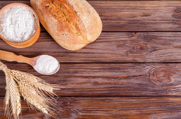 Ржаной деревенский хрустящий ломоть хлеба, мука и букет колосков на деревянном фоне.