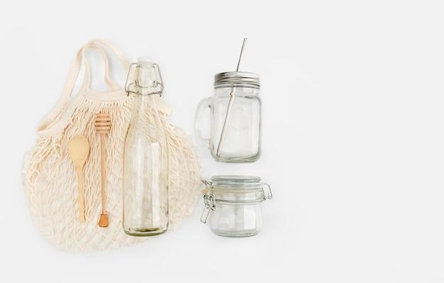 環境に優しいショッピングバッグ、水のボトル、蜂蜜ディップ、木のスプーンのセット。プラスチック無料のコンセプト。