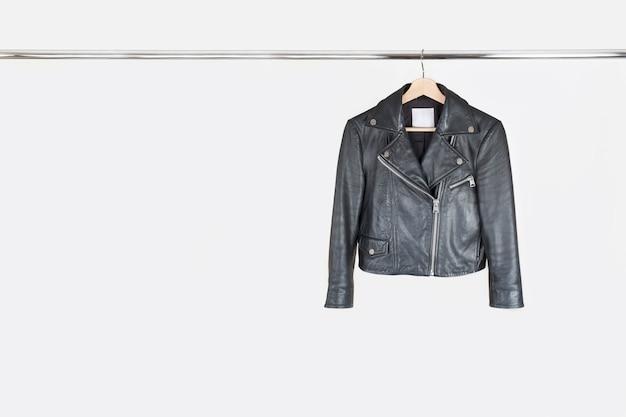 Модная кожаная куртка висит на вешалке на белом фоне