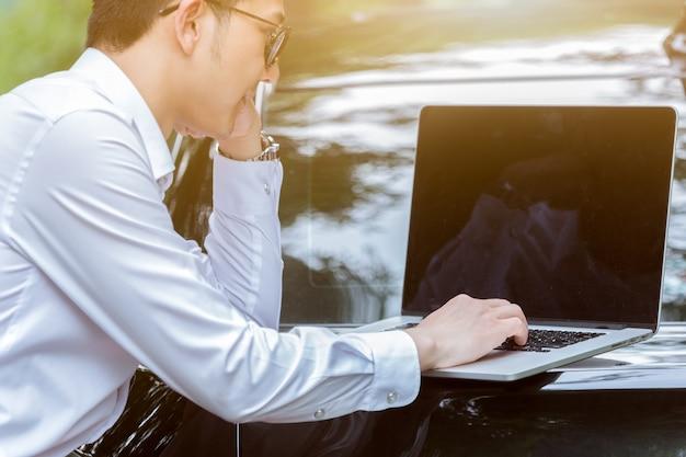 Деловые люди работают с ноутбуками на стороне автомобиля