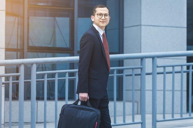 ビジネスマンはラップトップをオフィスビルの前で持ち歩いた