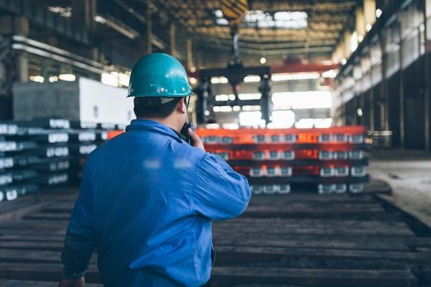 鉄鋼労働者は、スチールの持ち上げを指示するためにトランシーバーを使用した