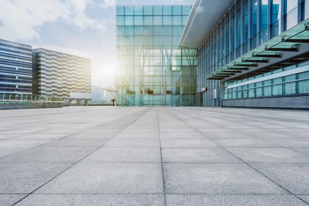 背景に現代的な建物がある空のレンガの床