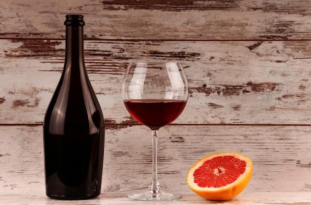 Бутылка красного вина на дереве, яблоко и гранат