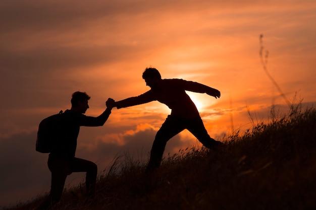 チームワークカップルのハイキングは、山、日没でお互いを支援シルエットを信頼します。