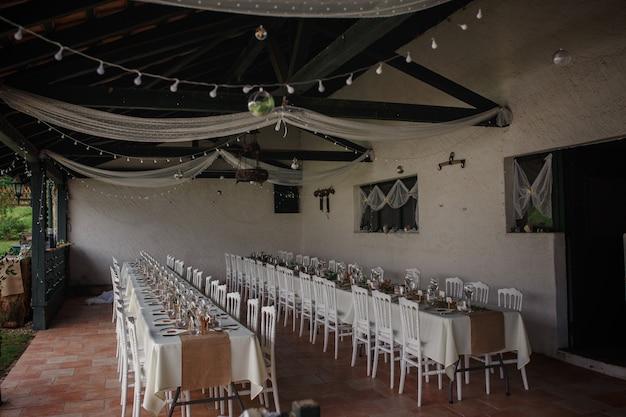 Ужин на открытом воздухе на свадьбе с украшением домашнего гарнира