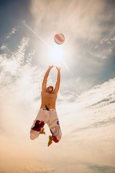 Игрок в мужской пляжный волейбол прыгает на горячий песок