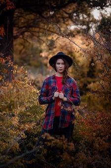 Красивая женщина позирует на лес осенью