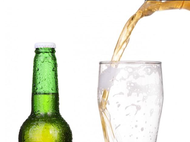 Разлива пива из бутылки на белом фоне