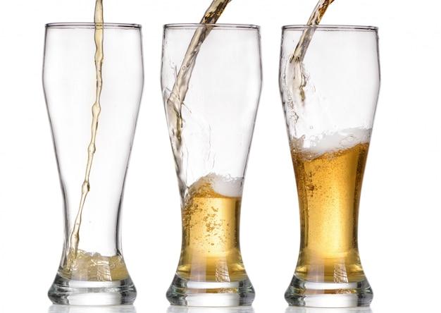 白い背景の上のビールの分離ガラスと茶色のボトル
