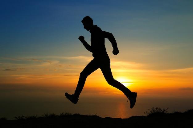 カラフルな空を背景に走っている男のシルエット。燃えるような夕日を背景に走っている人のシルエット