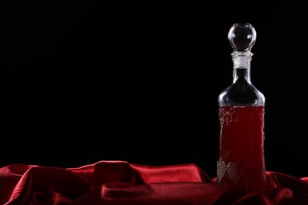 Бокал и бутылка вина на темном фоне шелка