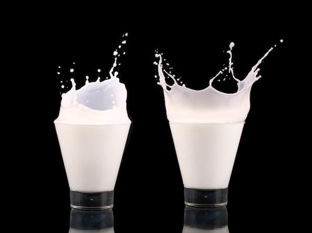 黒に分離された牛乳とガラスのスプラッシュ