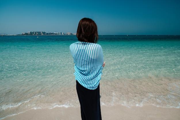 ドバイの海を歩いている女性の背面図