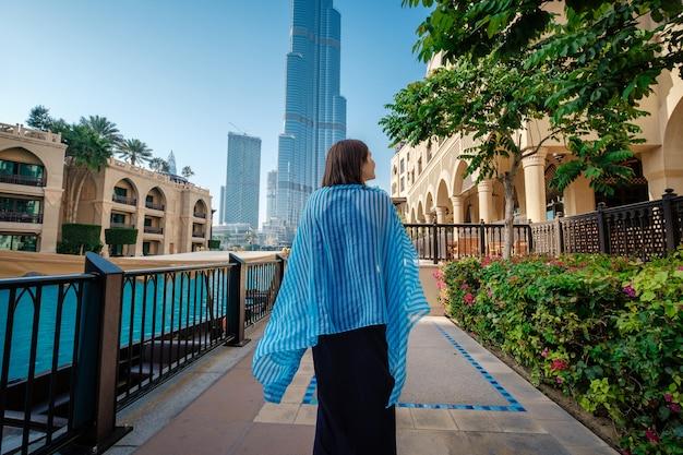 アラブ首長国連邦での旅行を楽しんでいます。ドバイのダウンタウンの上を歩いてドレスの若い女性。