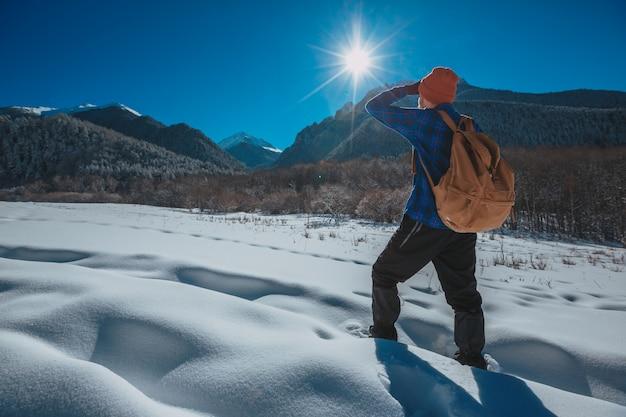 山でのトレッキングのバックパックを持つ男。寒さ、丘の上の雪。冬のハイキング。太陽と雪