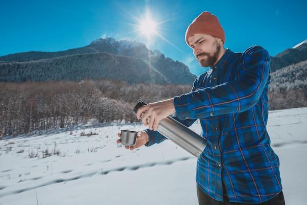Мужчина держит термос на снежной горе