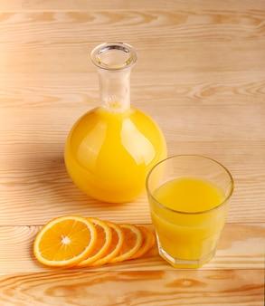 Свежевыжатый апельсиновый сок с нарезанными фруктами на деревянной стене