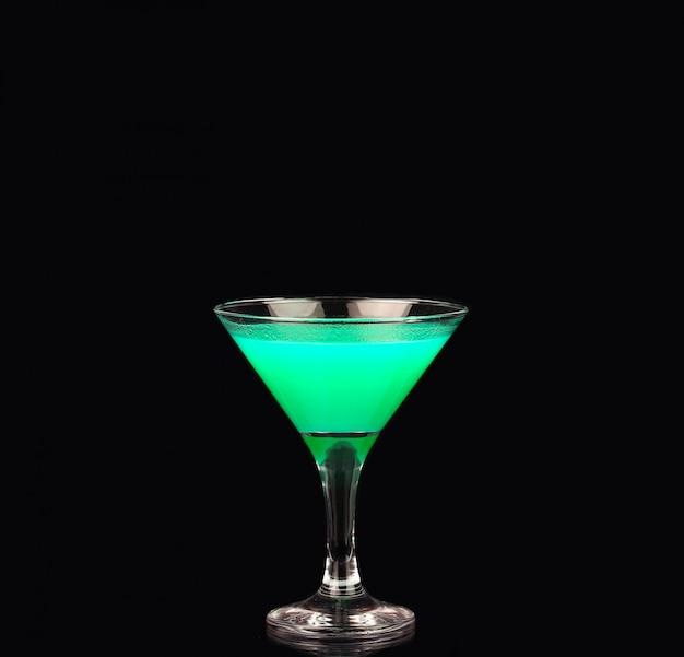 Бокал для мартини с зеленым коктейлем на черном
