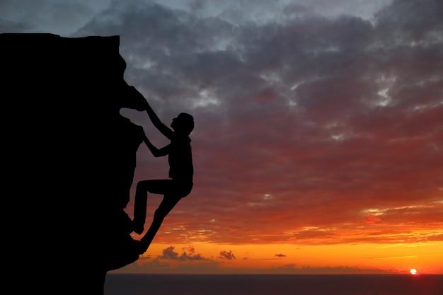 Совместная работа пара походы помогают друг другу доверять силуэт помощи в горах, закат. работа в команде мужчины и женщины, помогая друг другу на вершине альпинистской команды