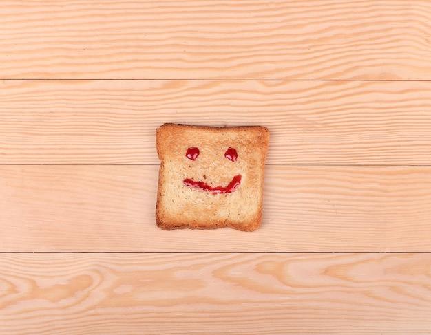 Кусочек хлеба с улыбкой на деревянном